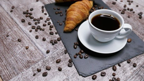 Isometric view of coffee beans, croissants and cappuccino
