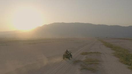 Jeep crossing an arid desert during sunset