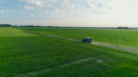 Jeep driving off-road on a green field