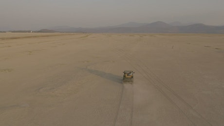 Jeep truck traveling through a desert seen from the air