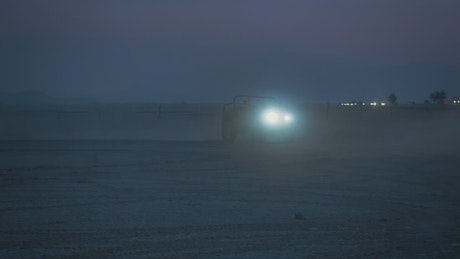 Jeep with headlights on in a desert at night