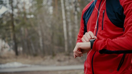 Jogger checks heart rate on smartwatch in forest