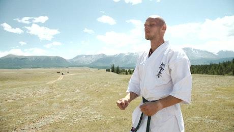 Karate black belt meditating in open field landscape
