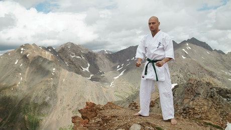 Karate black belt stands on mountain summit