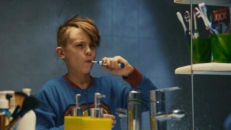 Kid brushing his teeth in the bathroom