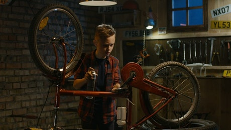 Kid repairs his bicycle in the garage