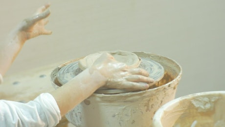 Kid working with clay on a pottery wheel