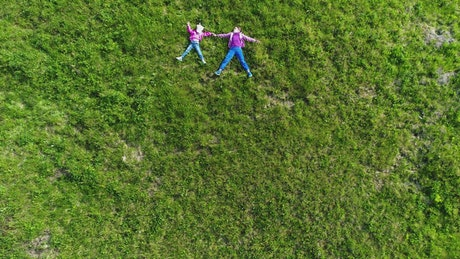 Kids layed in the grass, top aerial shot