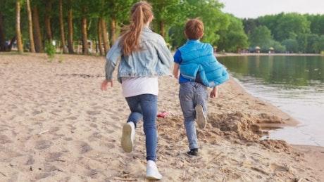 Kids running by a lake