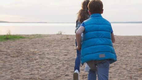 Kids running towards a large lake