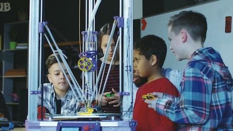 Kids watching a 3-D printer at school