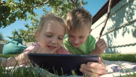 Kids watching tablet in the garden