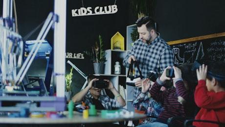 Kids with teacher exploring VR technology