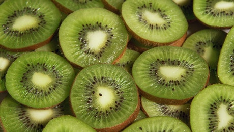 Kiwi fruit slices spinning on a plate