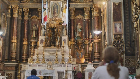 Lady praying in front of a large altar inside a church