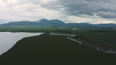Landscape of a great plain with a lake, trees and mountains around