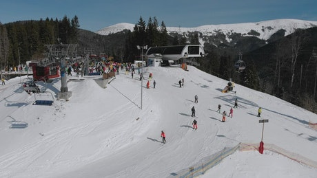 Landscape of sky lifts and skiers in the hill