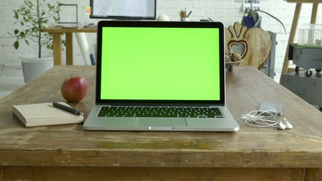 Laptop with a green screen over the table