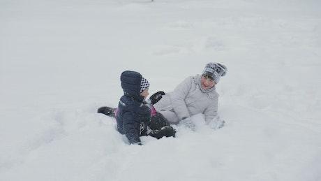 Laughing kids enjoy winter snowball fight