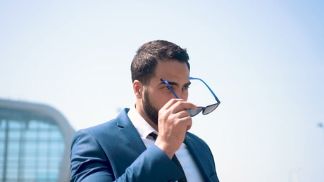 Lawyer puts on sunglasses in front of modern building