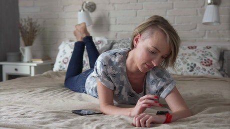 Laying on a bed checking her smartwatch