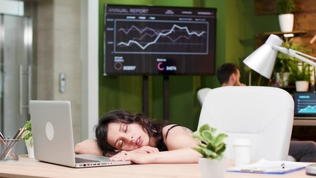 Lazy woman asleep at her desk in office