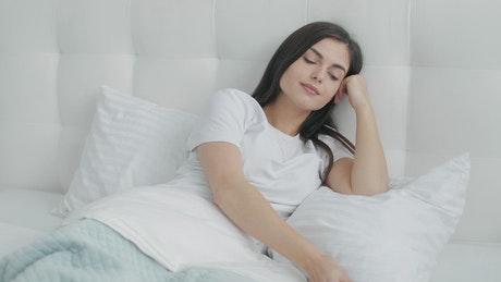 Lazy woman on mobile phone in bed