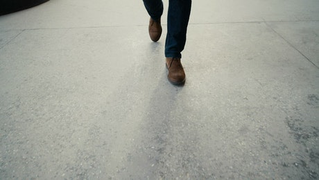 Legs of a man walking on the street