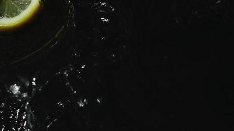 Lemon slices falling into dark water