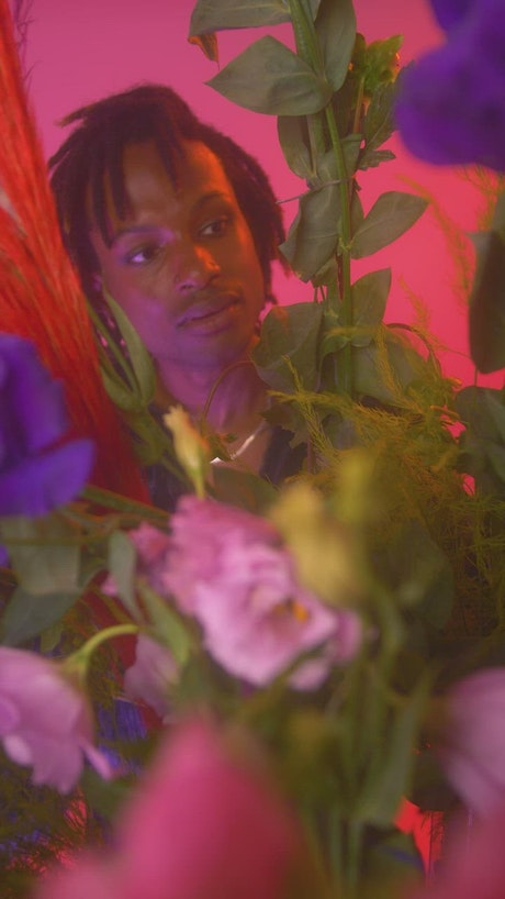 LGBTQ boy looking at camera surrounded by flowers