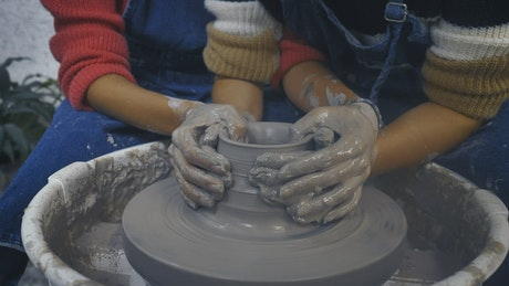 LGBTQ couple of girls making a clay vase together