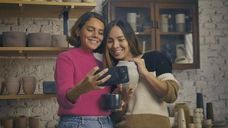 LGBTQ girlfriends taking a selfie in a pottery shop