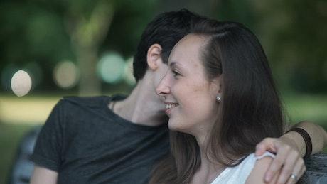 LGTBQ women kiss and talk on park bench