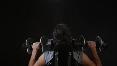 Lifting weights against a dark background