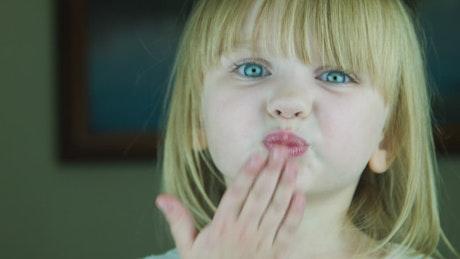 Little blonde girl send a kiss