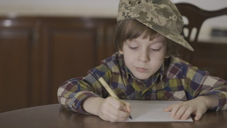 Little boy in Army hat writing letter to soldier