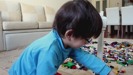 Little boy playing with many lego cubes
