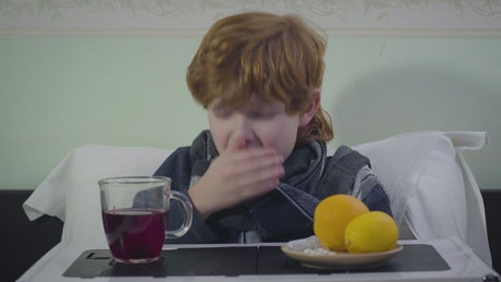Little boy sneezes while sick in bed with breakfast