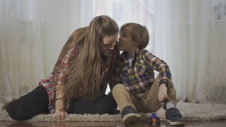 Little boy whispers secret in sister's ear