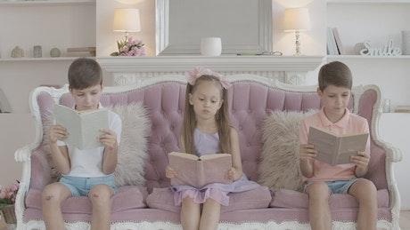 Little children reading stories in books