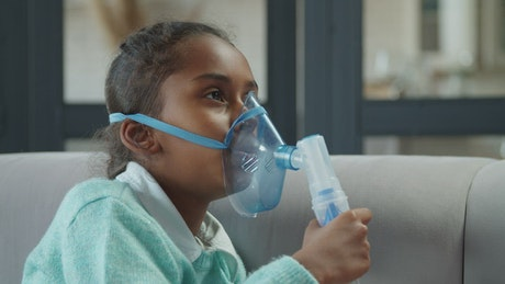 Little girl breathing from a nebulizer