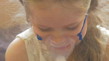 Little girl breathing with a facemask