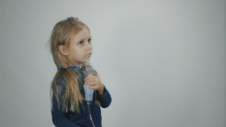 Little girl breathing with inhalation device