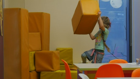 Little girl building a wall at school
