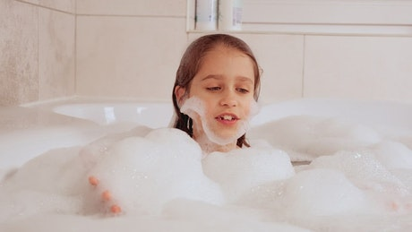 Little girl covered in foam in the tub