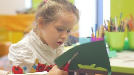 Little girl cutting paper in a kindergarten classroom