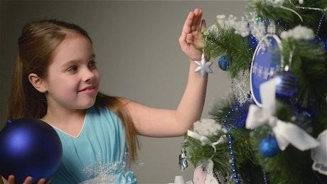 Little girl decorating her Christmas tree
