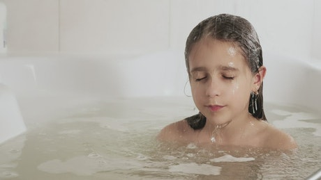 Little girl dipping her hair in the tub