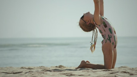 Little girl doing gymnastics on the beach