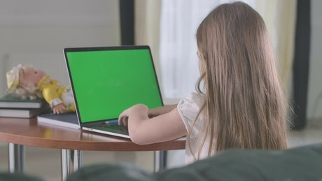 Little girl doing homework on a laptop